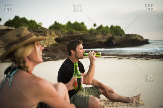 Couple sitting on beach, drinking beer, Nusa Lembongan, Indonesia