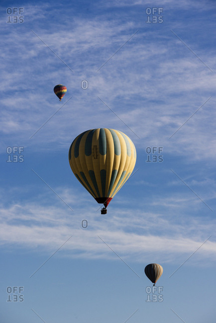 Three hot air balloons floating against blue sky, Goreme National Park, Cappadocia, Anatolia, Turkey