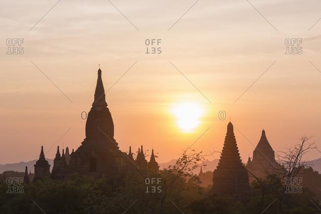 Silhouetted temples viewed from Dhammayazika Pagoda at sunset, Bagan, Mandalay Region, Myanmar