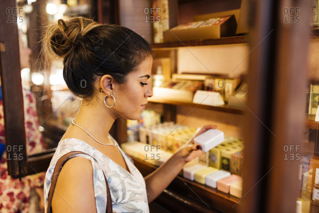 Side view of young woman looking at products for sale in Lisbon, Portugal