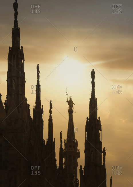 Sunset silhouetted statue of the Madonna (la Madonnina) on the highest spire of the Milan Cathedral, Italy