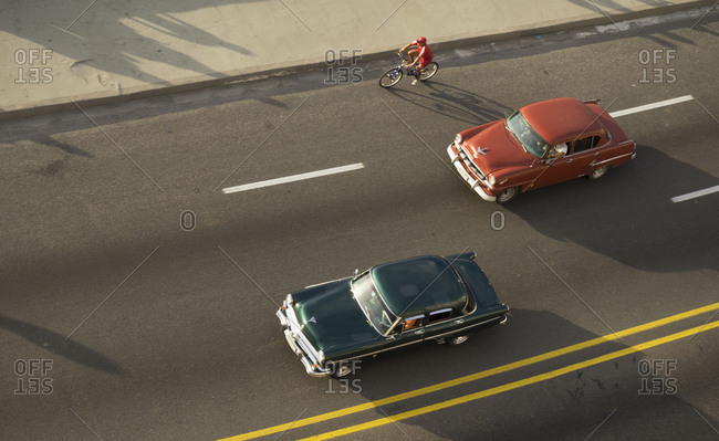 High angle view of cyclist and vintage cars on El Malecon, Havana, Cuba