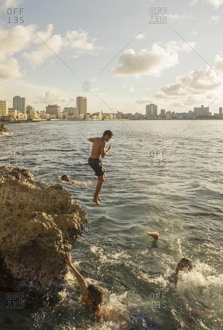 Boys jumping from rocks into sea, Havana, Cuba