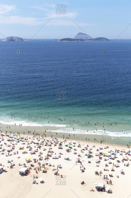 Tourists on beach, Cagarras islands in distance, Ipanema, Rio de Janeiro, Brazil
