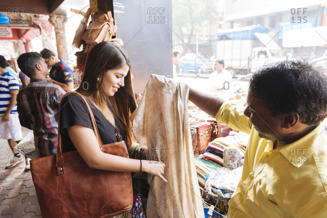Young female tourist looking at textiles on market stall, Mumbai, India