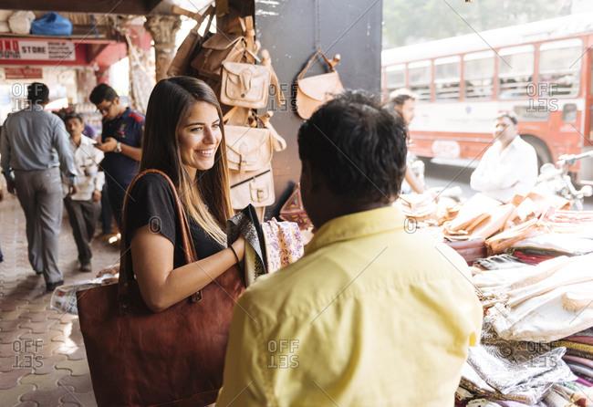 Young female tourist at textile market stall, Mumbai, India