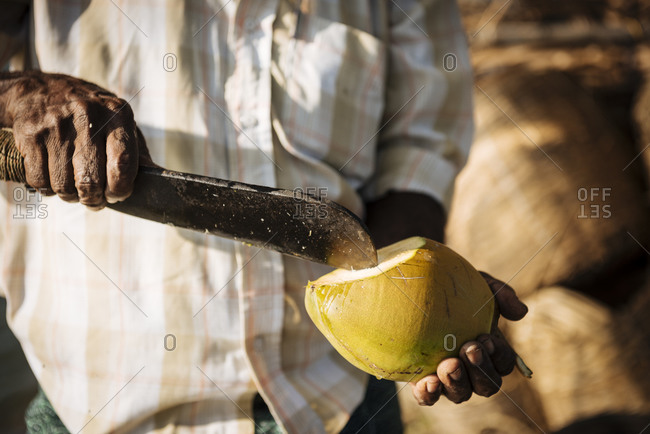 Man cutting coconut with knife