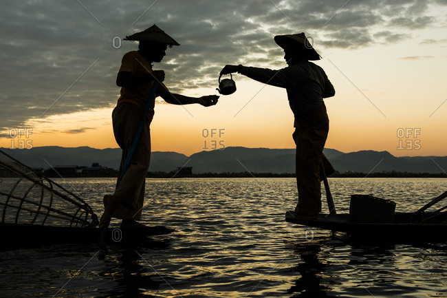 Two fishermen drinking tea at dusk, Inle lake, Shan State, Myanmar
