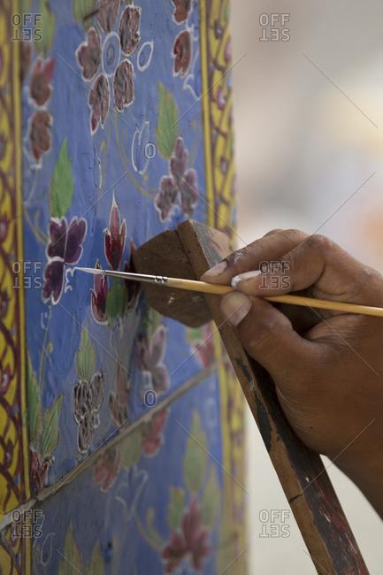 Hand painting ceramic tile at The Grand Palace, Bangkok, Thailand