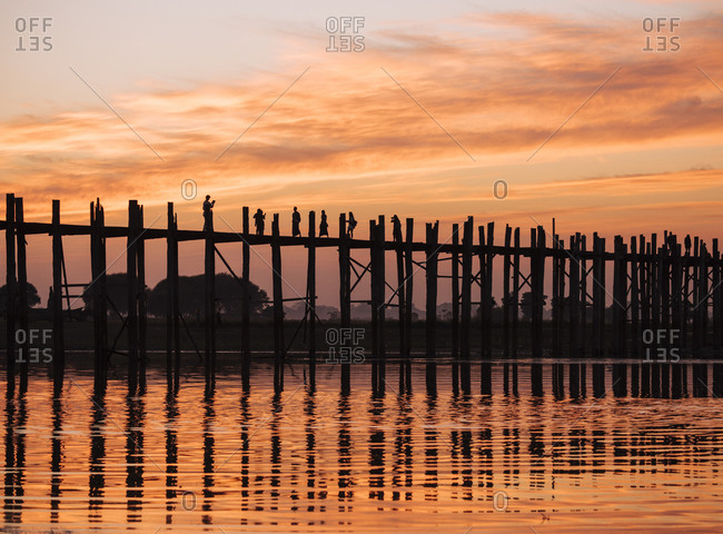 Silhouette of people on U Bein bridge at sunset, Mandalay, Mandalay Region, Myanmar