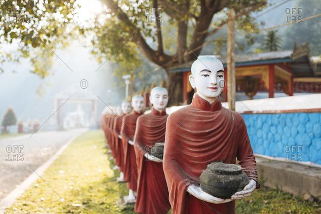 Row of buddhist monk statues holding ban bats, Kaw Ka Thawng Cave, Hpa An, Kayin State, Myanmar