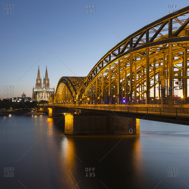 View of Cologne Cathedral (Koelner Dom) and Hohenzollern Bridge (Hohenzollernbruecke) crossing Rhine River at dusk, Cologne, Germany