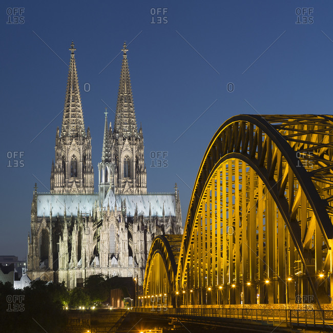 Hohenzollern Bridge (Hohenzollernbruecke) and Cologne Cathedral (Koelner Dom) spires at night, Cologne, Germany