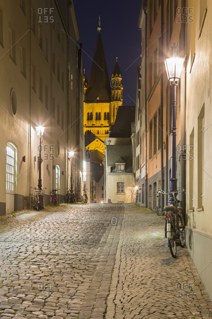 Cobbled alley and Great St Martin Church at night, Cologne, Germany