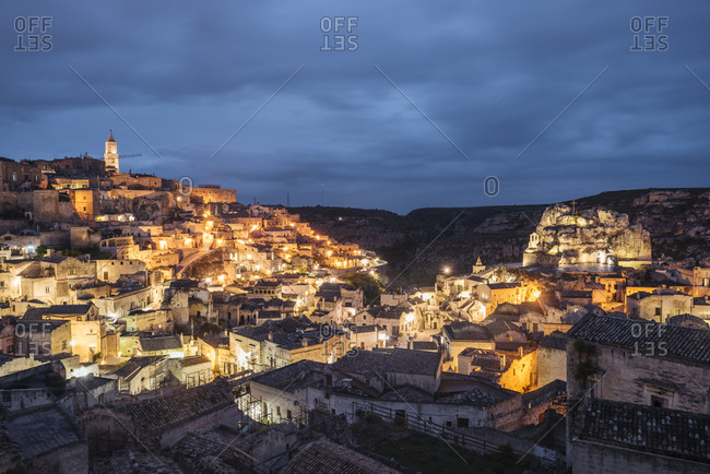 View of traditional building exteriors and city lights on hillside at dusk, Matera, Basilicata, Italy