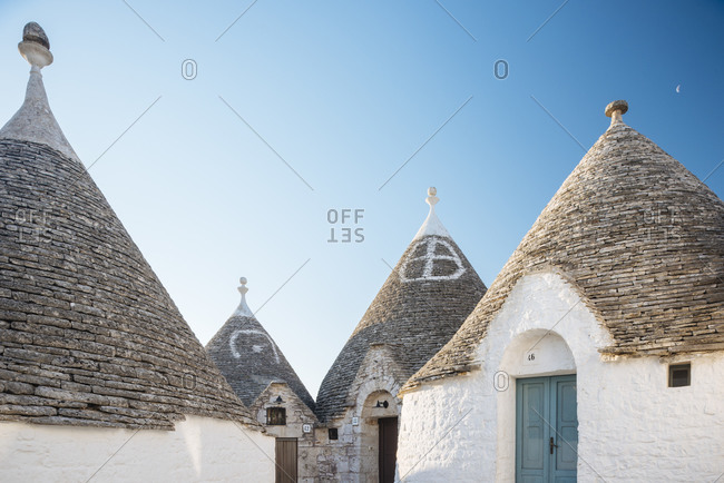 Four whitewashed trullo houses with conical roofs, Alberobello, Puglia, Italy
