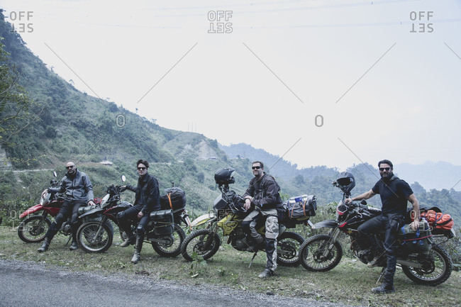 Four men with their motorcycles in rural landscape, Vietnam