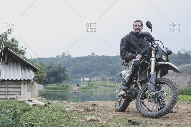 Man on motorcycle in rural landscape, Vietnam