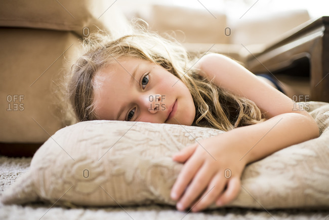 Young caucasian girl with long hair lying on a pillow relaxed on the floor with backlight