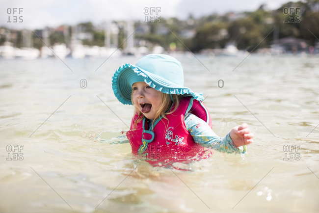 Caucasian toddler playing in the water with a blue hat