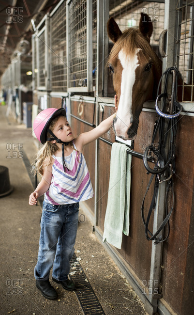 5 year old girl greeting brown horse in stable