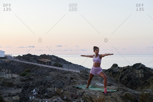 Fit young woman in sportswear practicing her warrior pose on a rocky coast in the early morning