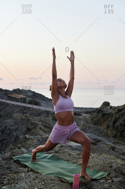 Fit young woman in sportswear practicing her crescent lunge pose on a rocky coast in the early morning