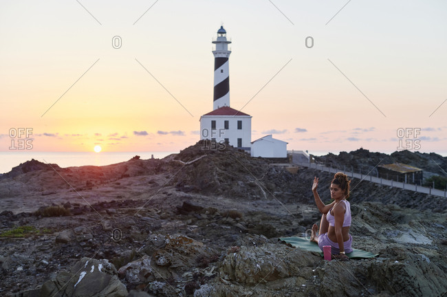 Fit young woman in sportswear doing the seated spinal twist pose on a mat outside by a lighthouse in the morning