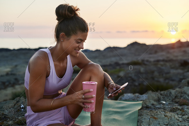 Smiling young woman in sportswear sitting outside on an exercise mat after yoga by the ocean and texting on her phone