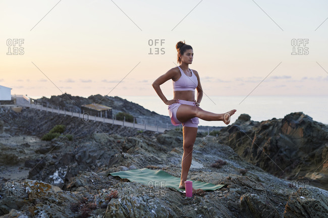 Fit young woman practicing the mountain one legged pose during a yoga session on a rocky coast in the early morning