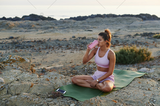Young woman in sportswear drinking water during a break from her yoga session outside on an exercise mat by the ocean