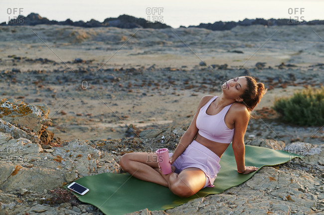 Young woman in sportswear taking a break from her outdoor yoga session by the ocean in the morning