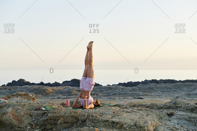 Fit young woman in sportswear doing a shoulder stand while practicing yoga on a rocky coast in the early morning