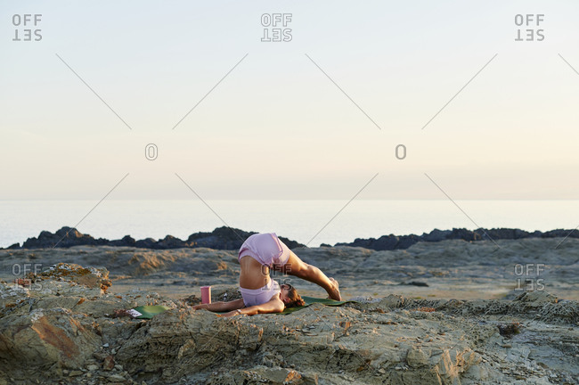 Fit young woman in sportswear practicing a shoulder stand during a yoga session on a rocky coast in the early morning