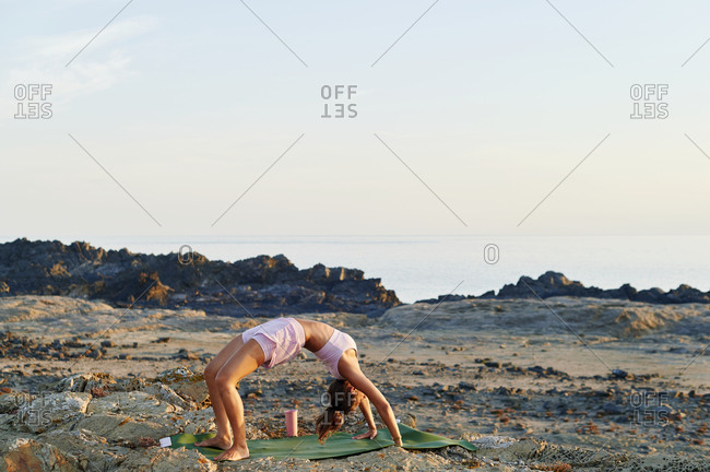 Fit young woman in sportswear practicing her wheel pose during a yoga session on a rocky coast in the early morning