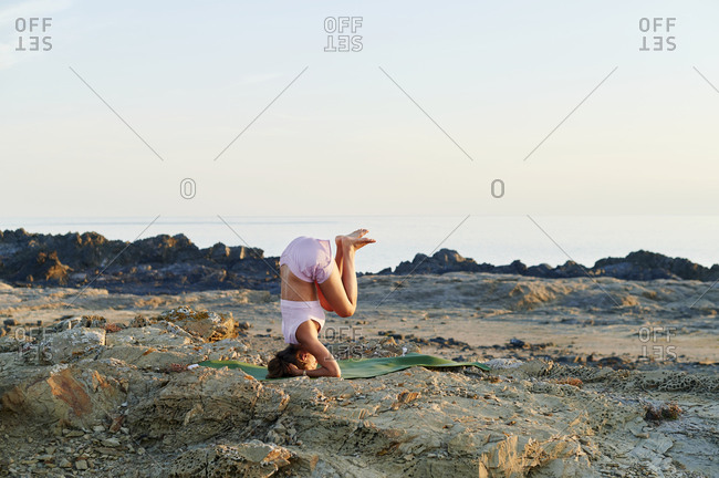 Fit young woman in sportswear doing a headstand during a yoga session on a rocky coast in the early morning