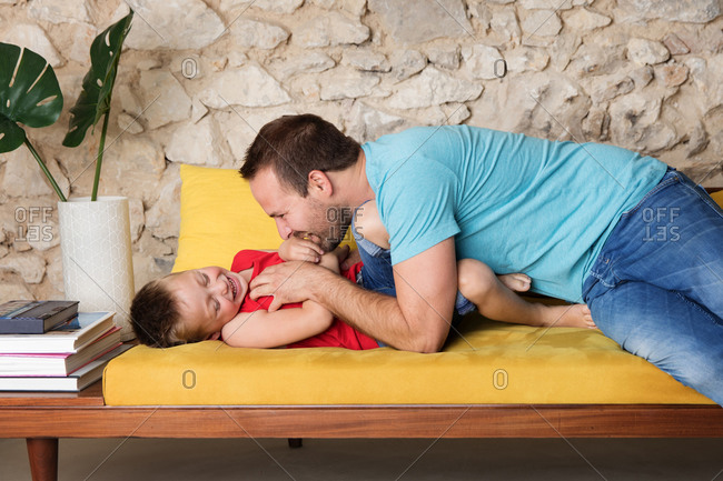 Happy father tickling laughing young boy on sofa at home