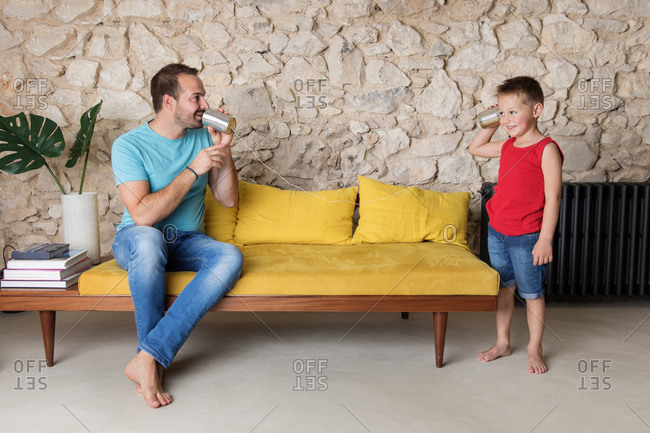 Father and son playing with tin can telephone on yellow sofa