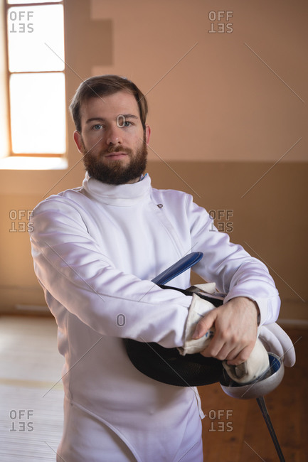 Portrait of Caucasian sportsman wearing protective fencing outfit during a fencing training session, looking at camera, holding an epee and a mask. Fencers training at a gym.
