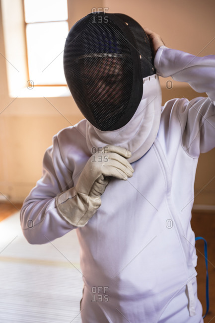 Caucasian sportsman wearing protective fencing outfit during a fencing training session, preparing for a duel, putting mask on. Fencers training at a gym.