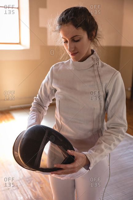 Caucasian sportswoman wearing protective fencing outfit during a fencing training session, preparing for a duel, holding a mask. Fencers training at a gym.