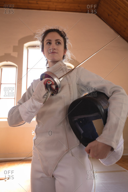 Caucasian sportswoman wearing protective fencing outfit during a fencing training session, preparing for a duel, holding an epee and a mask. Fencers training at a gym.