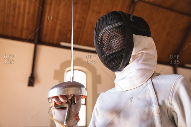 Caucasian sportswoman wearing protective fencing outfit during a fencing training session, preparing for a duel, holding an epee. Fencers training at a gym.