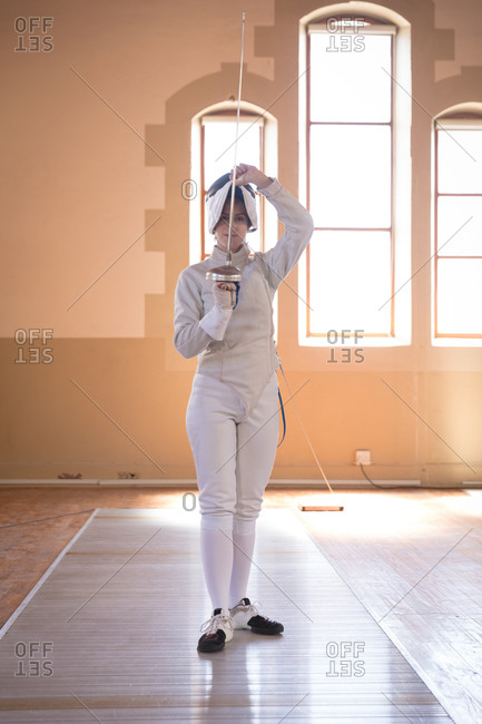 Portrait of Caucasian sportswoman wearing protective fencing outfit during a fencing training session, looking at camera and smiling, holding an epee. Fencers training at a gym.