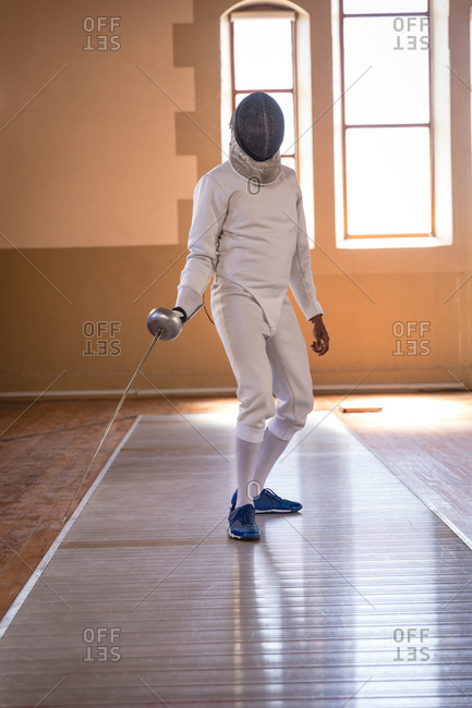 African American sportswoman wearing protective fencing outfit during a fencing training session, preparing for a duel, holding an epee. Fencers training at a gym.