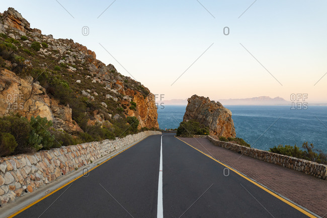 View showing an empty coastal asphalt road disappearing into the distance at the center of the image, cutting through mountains by the sea with a clear sky at sunset.