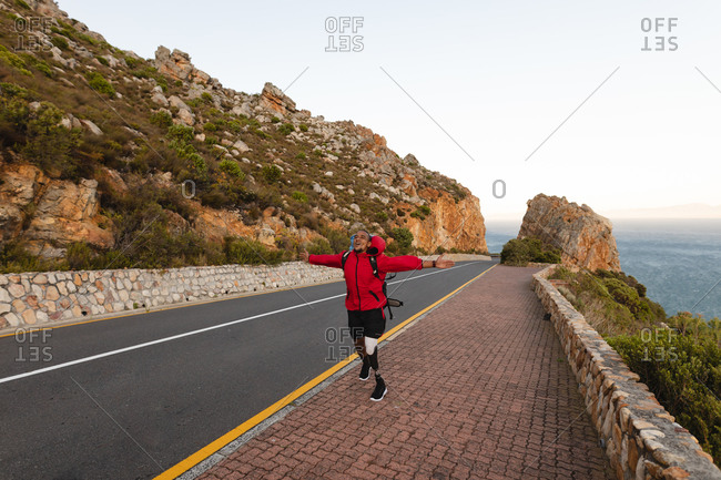 A fit, disabled mixed race male athlete with prosthetic leg, enjoying his time on a trip to the mountains, hiking with his arms outstretched on the road by the sea. Active lifestyle with disability.