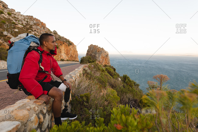 A fit, disabled mixed race male athlete with prosthetic leg, enjoying his time on a trip to the mountains, hiking, sitting on a wall on the road by the sea. Active lifestyle with disability.