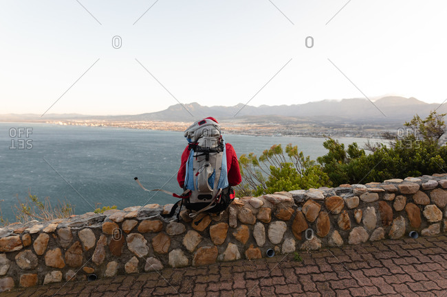Rear view of a disabled mixed race male athlete with prosthetic leg, enjoying his time on a trip to the mountains, hiking, sitting on a wall on the road by the sea. Active lifestyle with disability.