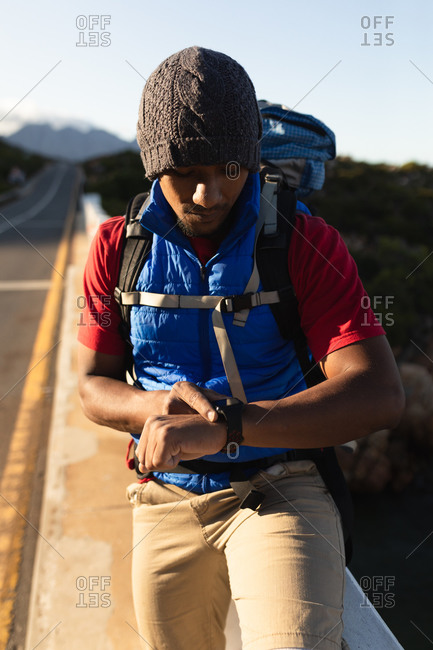 A fit mixed race male athlete, enjoying his time on a trip to the mountains, hiking, taking a break and checking his smartwatch. Active lifestyle mountain hiking.